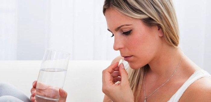 девушка пьет таблетки от боли эндометриоз