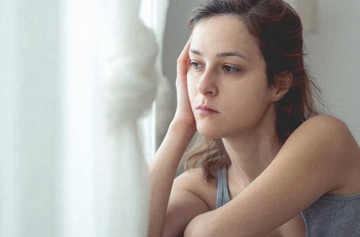 Молодая девушка у окна грустит
