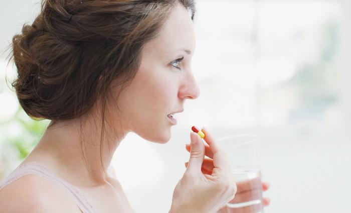 Женщина принимает противогрибковый препарат